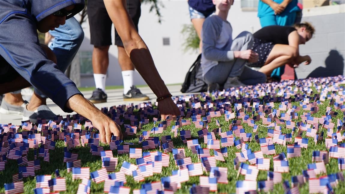 Students placing flags on lawn